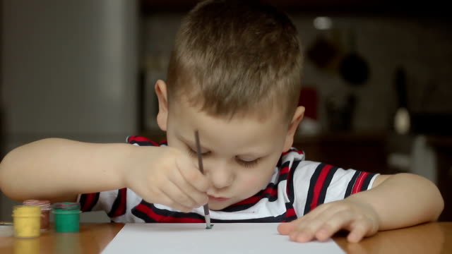 boy begins to draw paints video