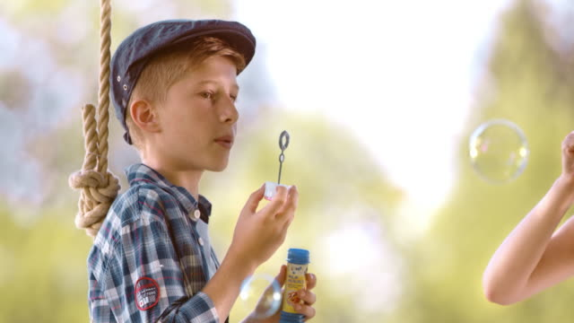 SLO MO Boy blowing bubbles on a swing with his friend video