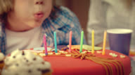 Boy blowing out the candles on a birthday cake video