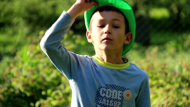 boy bows to the camera in the garden video