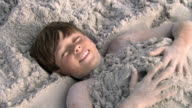 Boy buried in sand video