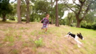 Boy chasing his running puppy dog in park with ball video