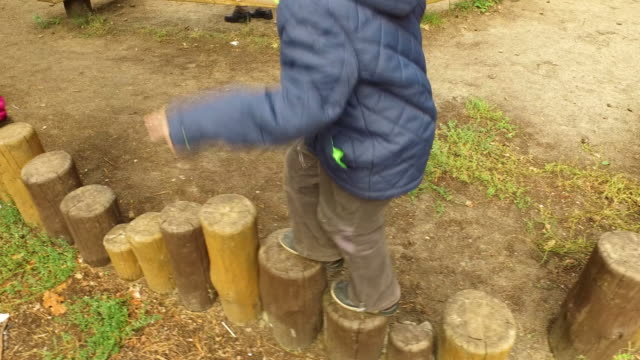 Boy child blond walking on stumps. The little boy is training to keep his balance. video