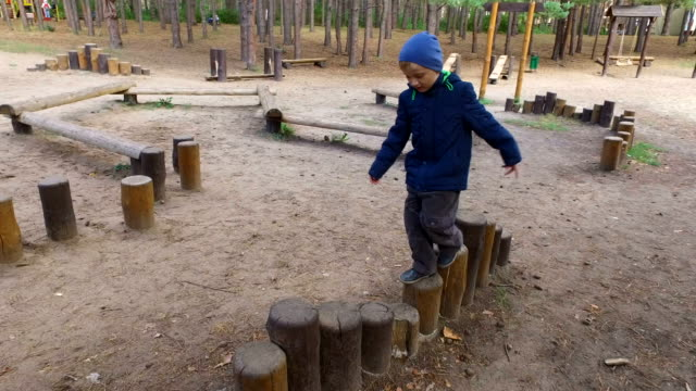 Boy child blonde is engaged in the wooden logs. Little boy playing on the playground. video