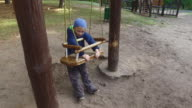 Boy child blonde swinging on a swing. Little boy shows how to swing on the swings. video