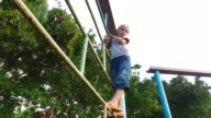 Boy child with white hair climbs onto the climbing frame. video