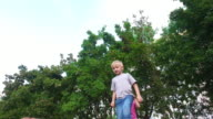Boy child with white hair makes jumps. Girl with glasses and with the ears jumping behind boy video