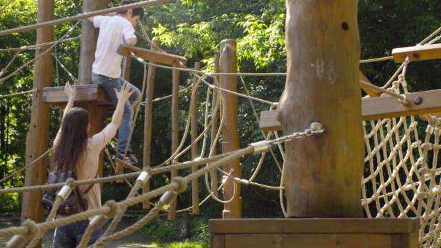 A boy climbing on a playground equipment video