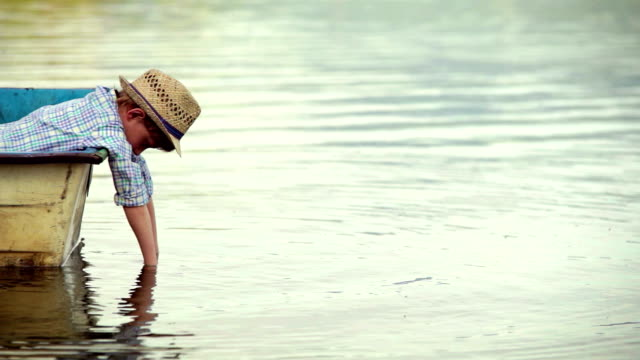 Boy dangles his hands in the water while leaning over the boat's board video
