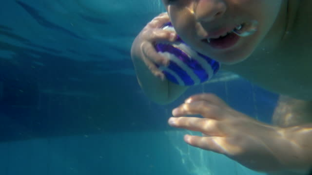 Boy diving and coming up from water in the pool video