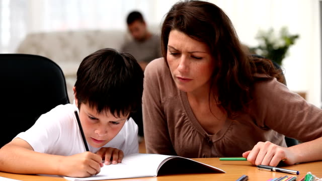 Boy doing homework with his mother video