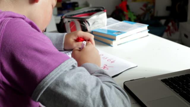 Boy Doing Math's Homework In Bedroom video