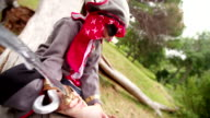 Boy dressing up as pirate sitting on log reading map video