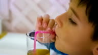 boy drinks juice through a straw video
