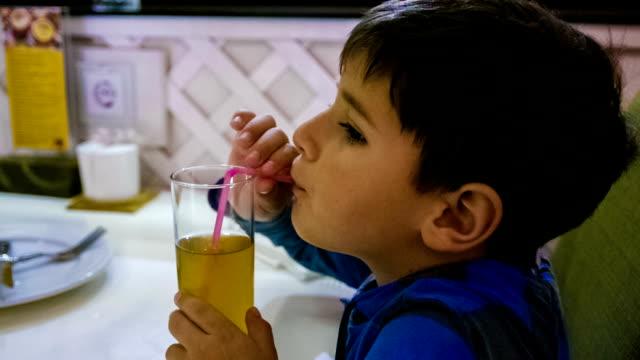 boy drinks juice through a straw video