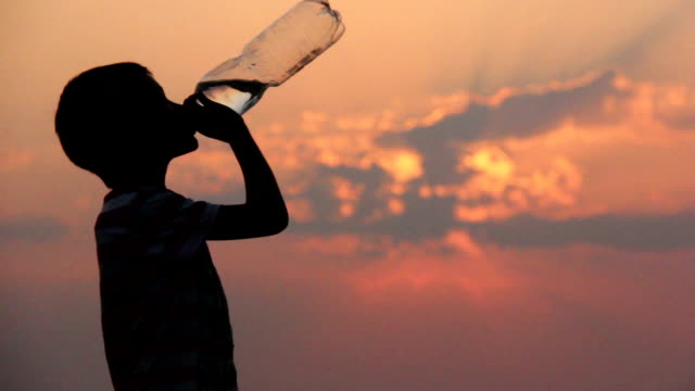 boy drinks water from a bottle at sunset, silhouette, teeneger video