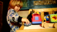 Boy Drives Automobile Toy on Table video