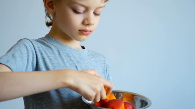 boy eating a peach, close up video