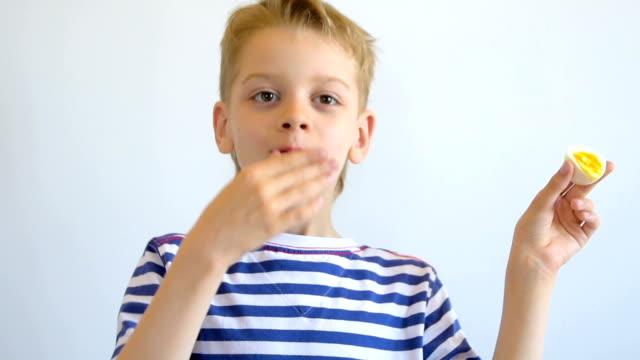 Boy eating boiled egg, close-up video