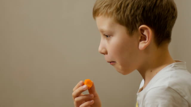 boy eating carrot indoors video