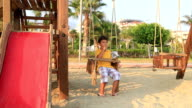 Boy eating chips on swing video