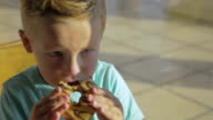 Boy eating chocolate donut and drinking water video