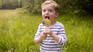 Boy Eating Colorful Lollipop video