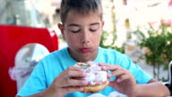Boy eating donuts in a bakery video