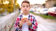 Boy eating fast food outdoors video
