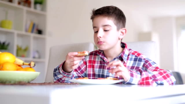 Boy eating pizza at home video