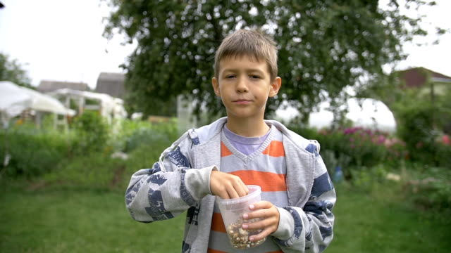 boy eating popcorn outdoors, slow motion video