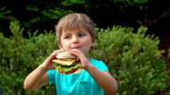 Boy eats a big burger with cheese video