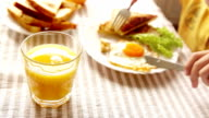 Boy eats his breakfast consisting of a fried egg, some toast and orange juice video