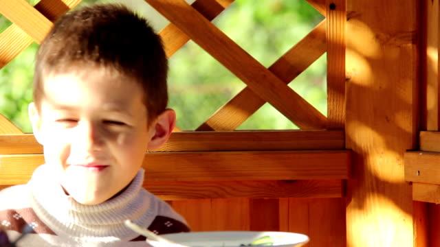 Boy eats in the gazebo outdoors, sleepy boy, camera shy video