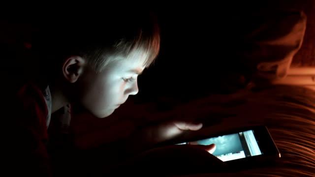 Boy enjoy digital tablet at night video