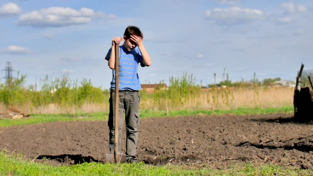 boy farmer weary digs ground old dirty shovel on dry ground slow motion video video