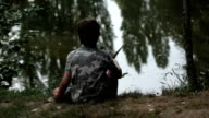 boy fishing seen from the back video