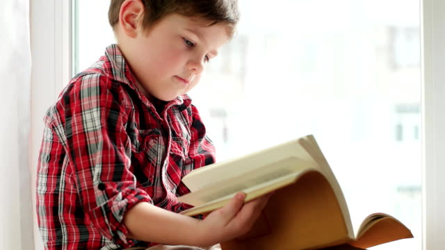boy flipping pages, little child wearing shirt sitting on window with old book in orange cover video