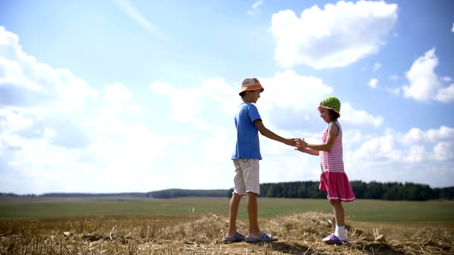boy gives a girl a flower in a field girl glad gift of flower, love concept video