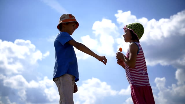 boy gives a girl a flower on a sky background, gift of glad girl, love concept video