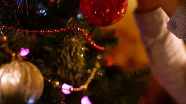 Boy hangs a ball on the Christmas tree in the new year video