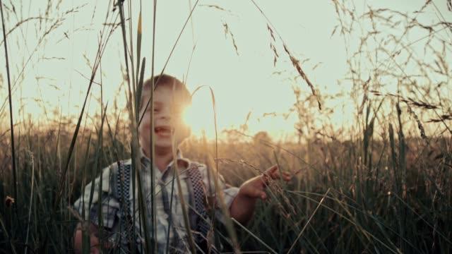 SLO MO Boy having fun in grass video