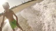 Boy having fun on sea waves at summer vacation video