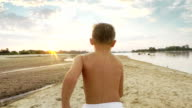 Boy having fun. Race along the shore video