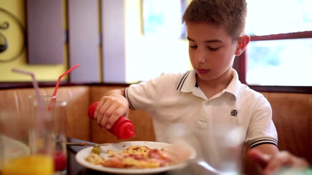 Boy having lunch in a restaurant video