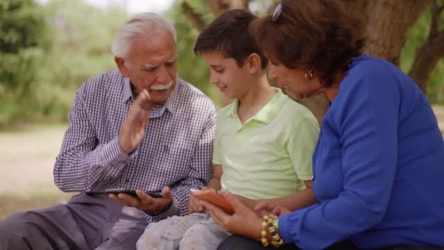 Boy Helping Grandpa Surfing Internet On Mobile Phone video