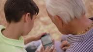 Boy Helps Senior Man Grandfather Using Mobile Phone video