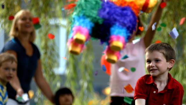 Boy hitting a pinata at party, slow motion video