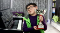 boy holding silver medal cup by the piano video