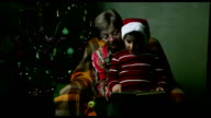 boy in a New Year's cap with a book sitting on their hands at the grandmother on a background of the Christmas tree video
